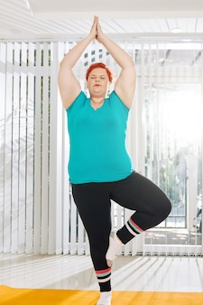 Plus size woman in tree position