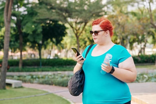 Плюс размер женщина гуляет в парке