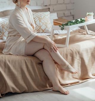 얼굴을 알아볼 수 없는 플러스 사이즈 여성은 란제리와 실크 가운을 입고 실내 침대에 앉아 있습니다.