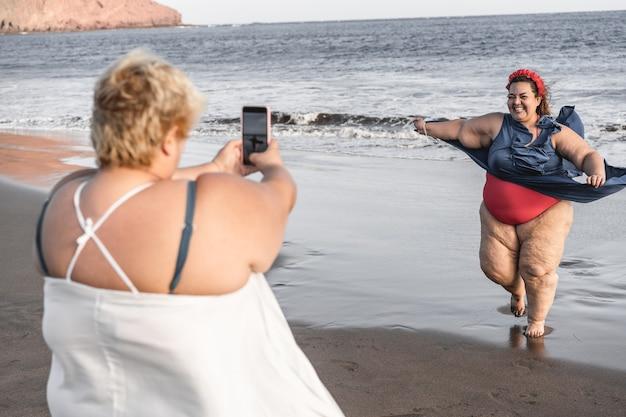 플러스 사이즈 여자 친구가 해변에서 사진을 찍는 재미