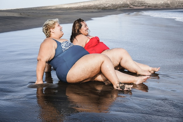 Plus size women sitting on the beach having fun during summer vacation