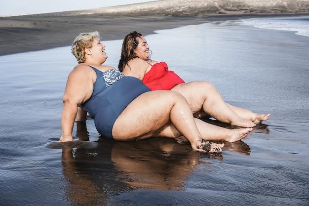 夏休みの間に楽しんでビーチに座っているプラスサイズの女性