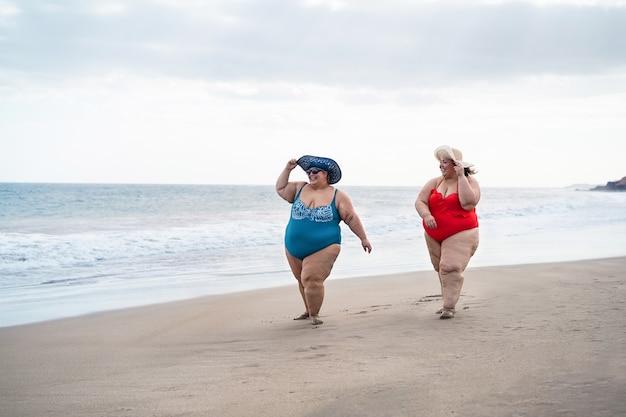 プラスのサイズの女性が夏休み中にビーチを歩いて-一緒に笑っている曲線美の女性-太りすぎの体と旅行のコンセプト