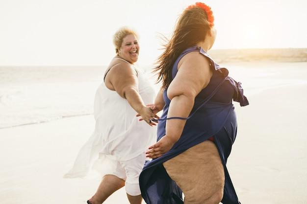 Женщины больших размеров гуляют по пляжу и веселятся во время летних каникул - сосредоточьтесь на правильной девушке