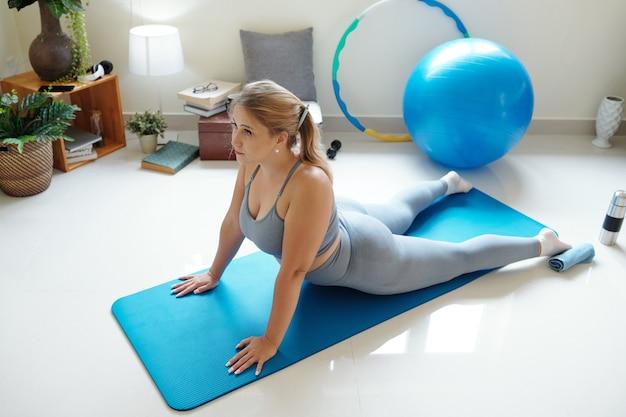 Молодая женщина большого размера делает упражнения на коврике для йоги дома, она практикует позу кобры, чтобы укрепить свой позвоночник
