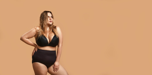 Плюс размер молодой женщины в сексуальном черном белье глядя в сторону, стоя на коричневом фоне
