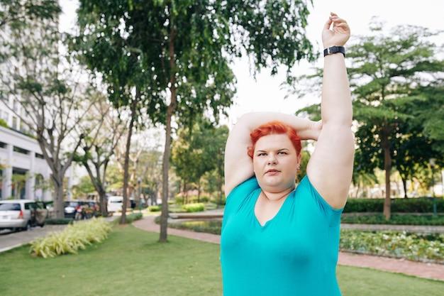 プラスのサイズの若い女性が腕を伸ばす