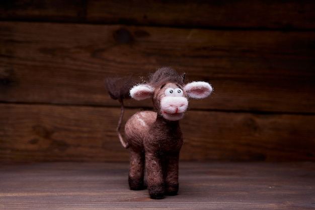 Plush bull toy on a wooden background. a soft toy greets the viewer. symbol of 2021 new year.