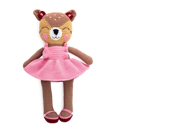 Plush crocheted cat with a pink dress on white surface