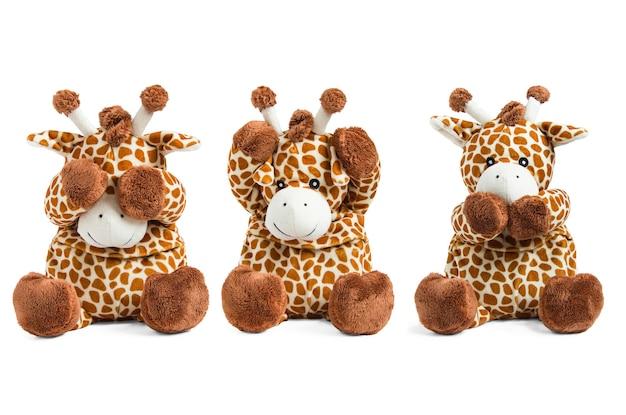 白い背景で隔離のぬいぐるみキリンのおもちゃは、柔らかい茶色のおもちゃの色の目、鼻、耳をカバーしています