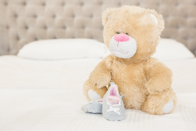 Plush and infant shoes on bed