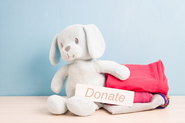 Plush puppy and children's clothing for a donation