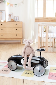 豪華なウサギは子供部屋のビンテージレーシング子供の車に座っています。北欧スタイルのインテリア。子供の寝室のレトロなスタイルのベビーカー。幼稚園の子供向けのおもちゃ。素朴。ヒゲ