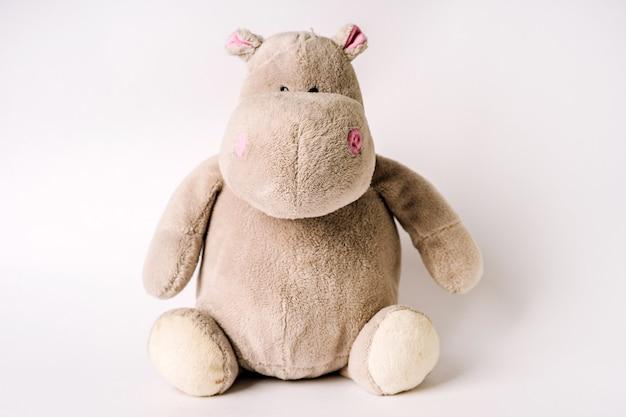 Плюшевая игрушка бегемот сидит на белом фоне