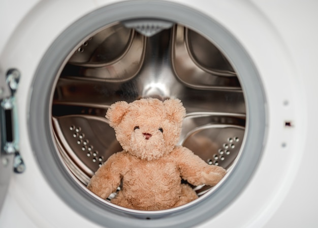 Plush teddy bear after washing in machine sitting inside with open door