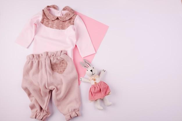 Плюшевая игрушка и детская одежда вид сверху