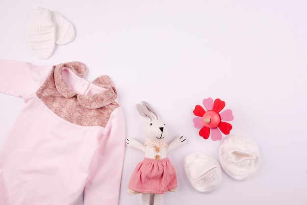 Plush toy and baby clothes flat lay