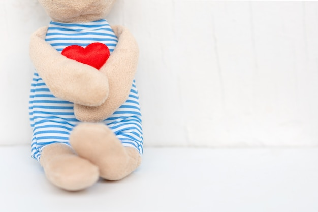 Plush toy bear holding red heart in his hand on white with love
