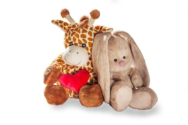 봉제 장난감 기린과 토끼 토끼는 흰색 배경에 고립 된 붉은 마음을 잡고