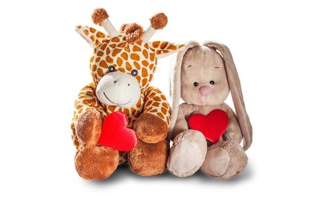봉제 장난감 기린과 토끼 토끼 잡고 흰색 배경에 고립 된 붉은 마음 화려한 봉제 장난감