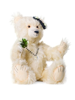 Plush toy polar bear with beads and a bouquet of flowers isolated on white background