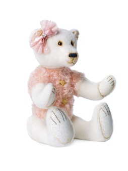 Plush toy polar bear with a pink butterfly on its head on a white background