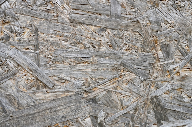 Plywood gray color. background texture of aged sheet of plywood with fragments of compressed sawdust