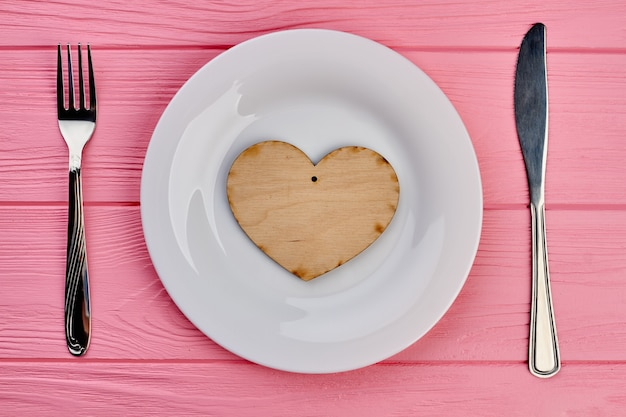 Plywood heart on white plate. table setting for valentines day with plate, wooden heart, fork and knife. happy valentines holiday.