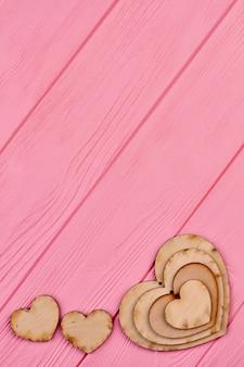 Фанерные сердечки для украшения, копия пространства. день святого валентина или свадебный баннер с деревянными сердцами, вид сверху. декоративная деревянная форма сердца.