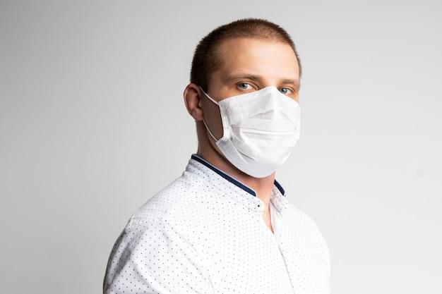 Молодой человек носит маски, чтобы предотвратить загрязнение воздуха, дымку и pm 2,5 пыли и дыма загрязнения на белом. медицинская защита от болезней, передающихся по воздуху, коронавирусов. человек боится заболеть гриппом