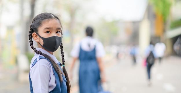 アジアの女の子がpm 2.5のほこりと大気汚染を保護するためにマスクを着用