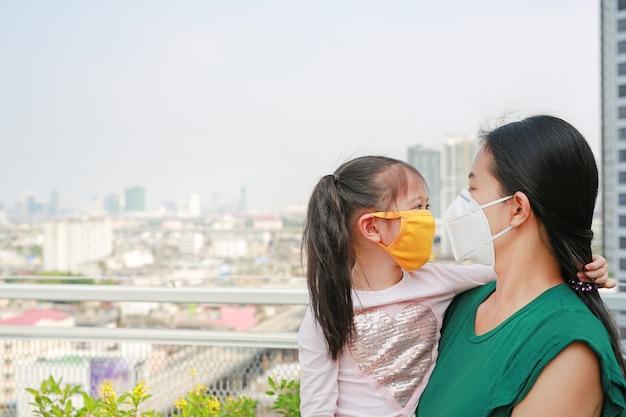 バンコク市内のpm 2.5大気汚染に対する保護マスクを身に着けている彼女の娘を運ぶアジアの母親。タイ。