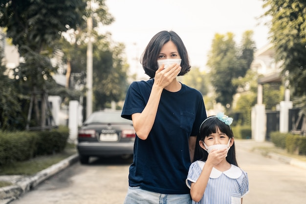 アジアの女性とマスクを身に着けている小さな若い娘は、家の外の夕暮れpm 2.5の悪い大気汚染を防ぎます。