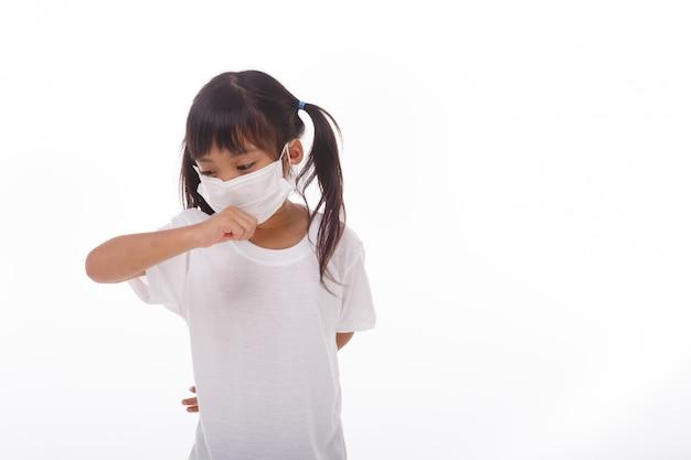 ウイルスを防ぐためにマスクを身に着けているアジアの女の子pm2.5、コロナウイルス、(2019-ncov)冷たいまたは肺炎の症状として、気分が悪く、咳をしているアジアの小さな女の子、白い背景の上