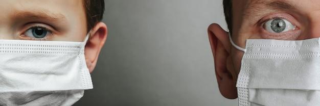 男と灰色の背景にフェイスマスクを持つ少年。コロナウイルスと大気汚染pm2.5の概念。 covid-19(新型コロナウイルス感染症)(#文字数制限がない場合、初出時にかっこ書きを追加