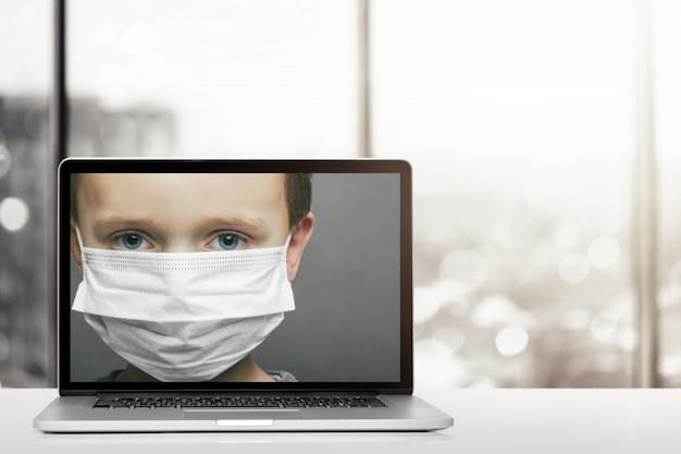 Разговор онлайн через портативный компьютер у себя дома. мальчик в маске со страхом в глаза крупный план в мониторе компьютера. концепция коронавируса и загрязнения воздуха pm2.5. covid-19