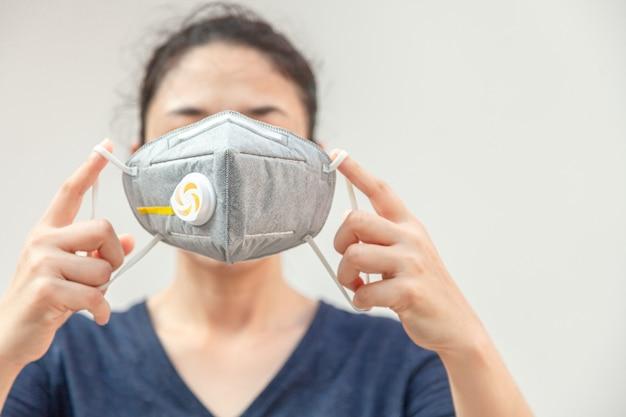 ウイルスpm2.5およびコロナウイルスまたはcovid-19を防止するために衛生マスクを着用している女性。環境意識