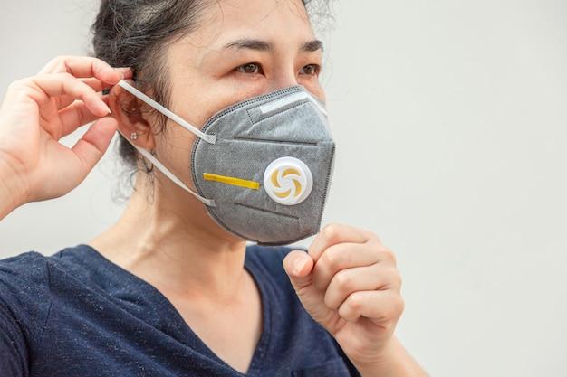 ウイルスpm2.5およびコロナウイルスまたはcovid-19を防止するために衛生マスクを着用している女性。
