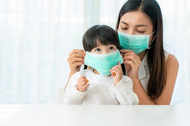 Pm2.5のほこり、スモッグ、大気汚染、covid-19を防ぐために、自宅のリビングルームに座っている娘の健康的なフェイスマスクを身に着けているアジアの母親。