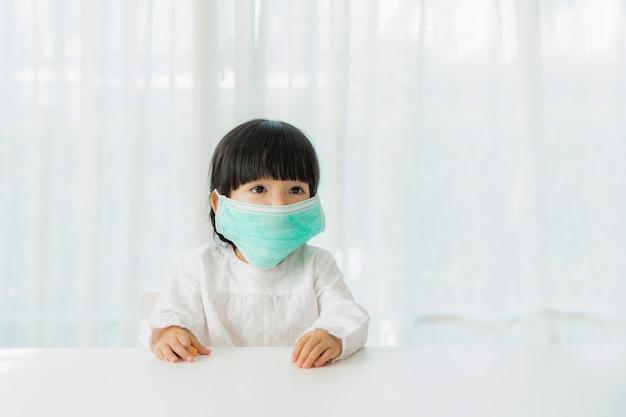 Маленькая китайская девушка нося здоровую лицевую маску сидя в живущей комнате дома для того чтобы предотвратить пыль pm2.5, смог, загрязнение воздуха и covid-19.
