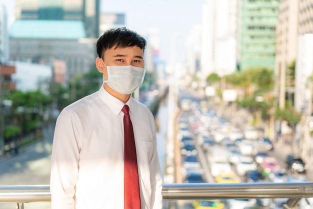 Молодой стресс азиатский бизнесмен в белой рубашке собирается работать в городе загрязнения. она носит защитную маску, предотвращающую попадание пыли pm2,5, смог, загрязнение воздуха и covid-19.