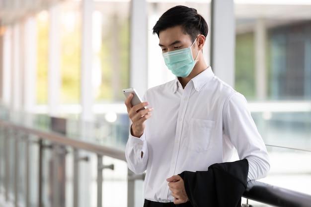 Молодой азиатский человек носит медицинский лицевой щиток гермошлема для защиты коронавируса и руки pm2.5 держа мобильный телефон.