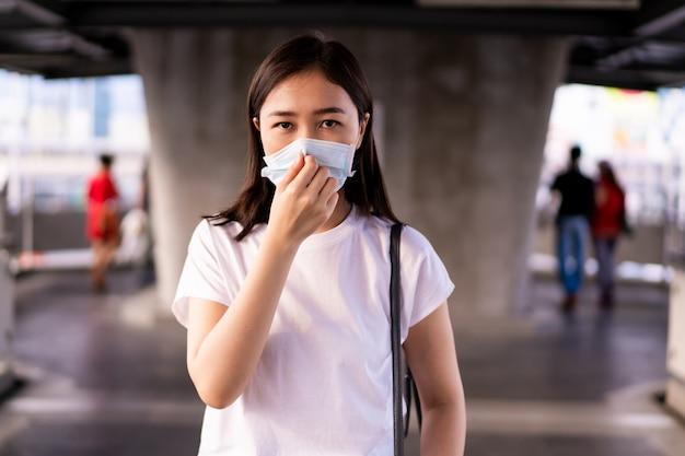 Красивая молодая азиатская женщина нося защитную маску пока путешествующ в городе где полно с загрязнением воздуха pm2.5.