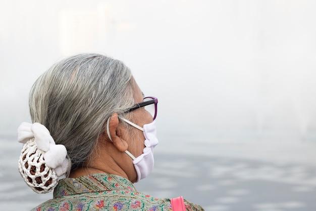 Старая женщина нося маску pm2.5 защищает коронавирус, пыль опасности в бангкоке юго-восточной азии