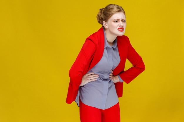 빨간 양복을 입은 pms 빨간 머리 비즈니스 여성은 기간 복통이 있습니다