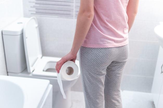 ロール紙を保持し、トイレで下痢、便秘、膀胱炎に苦しんでいる女性。 pms中の胃の痛み