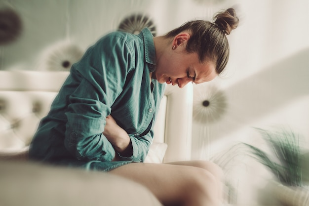 自宅の寝室でpmsと月経痛に苦しんでいる若い人。重大な日のために胃の痛み、腹痛がある。炎症および感染膀胱、膀胱炎。