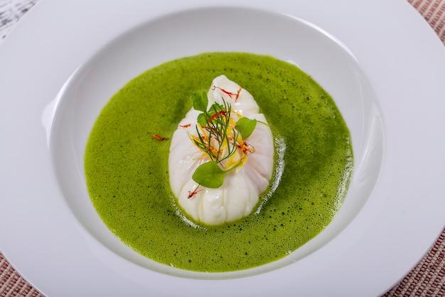 Яйцо-пашот и зеленый здоровый соус, крупным планом в белой тарелке