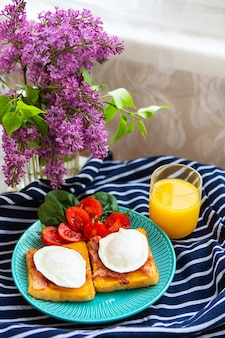 Poached egg on toasted english toast with spinach, cherry tomatoes, orange juice