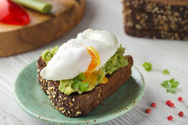 Poached egg on wholemeal brown toast with dip avocado